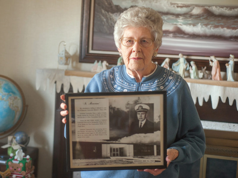 "Ruth Young holds a photo of her brother, Navy pilot Lt. Cmdr. Richard ""Dick"" Clark Perry, who died in combat 50 years ago in Vietnam. Photo by Sarah Spratling"
