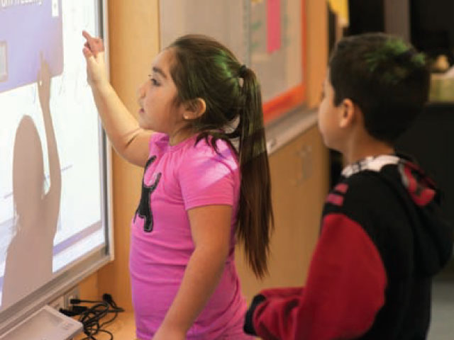 Second-grader Miranda works at a digital whiteboard during class.