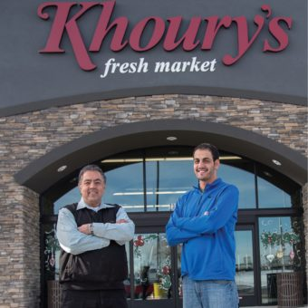 Two men standing outside of a supermarket. Sign reads: Khoury's Fresh Market