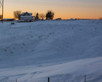 A home in the distance on snow covered ground at sunset