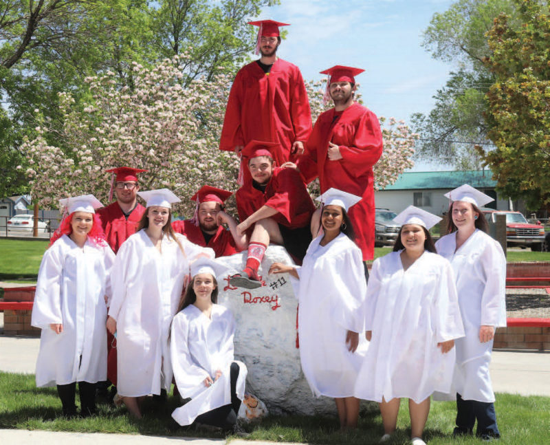 High school seniors wearing red and white cap and gowns
