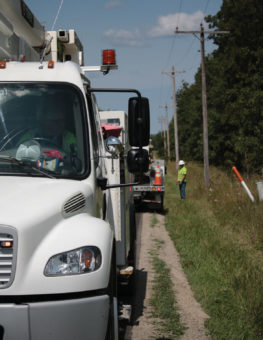 closeup of front of bucket truck with lineman working on power poles in back