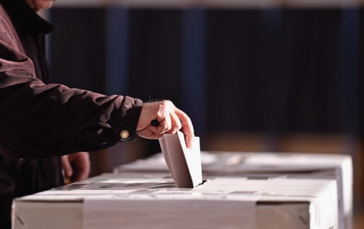 Photograph of person inserting a folded piece of paper into a ballot box