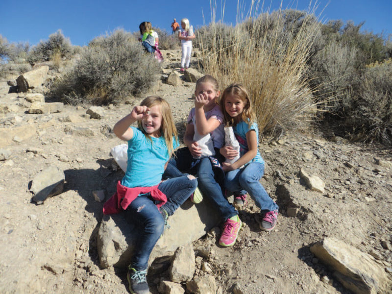 Young girls holding up their fossils.