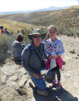 Geologist Jon Powell with a young girl outside in a valley.
