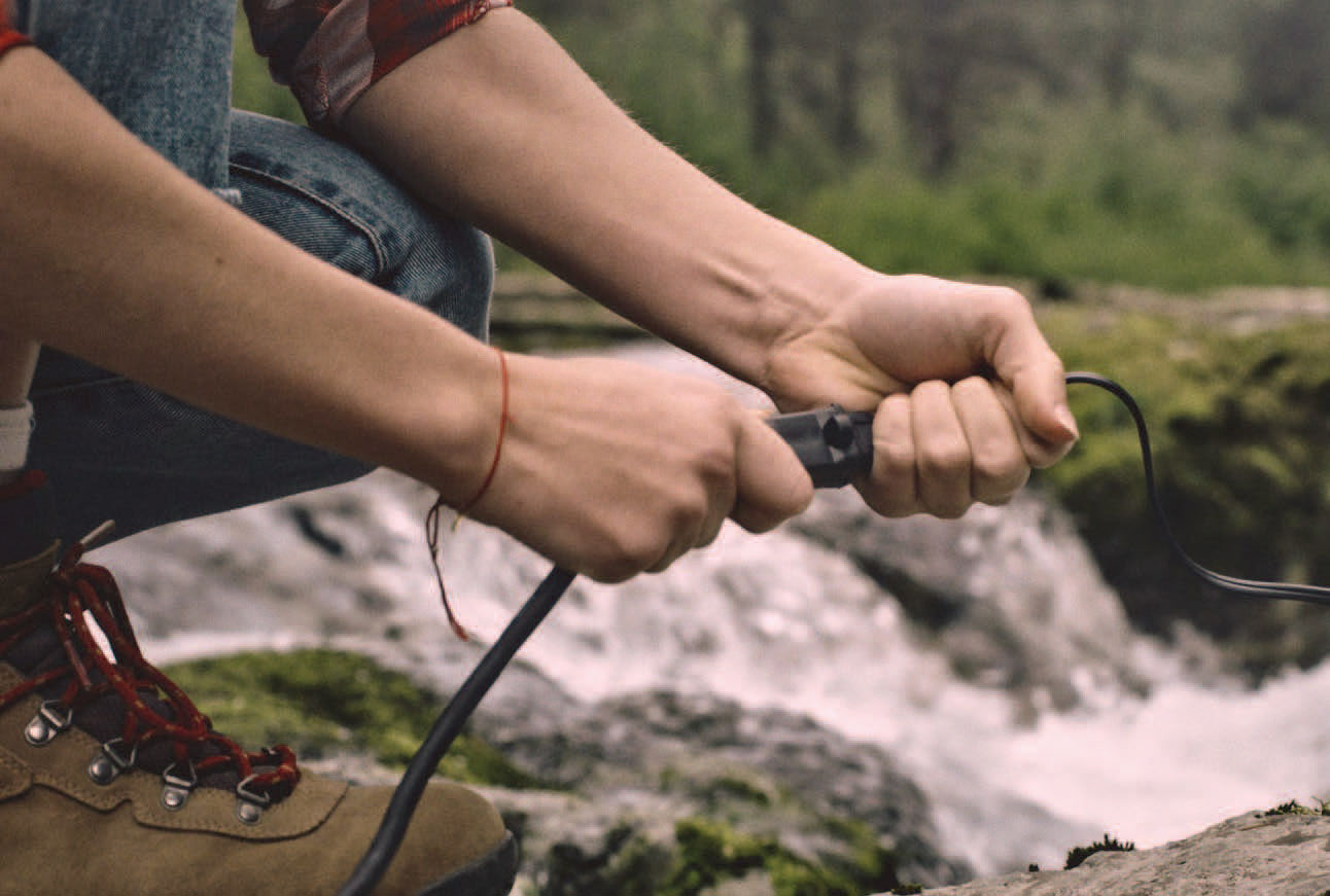 Person's hands plugging in a cord while standing near a river.