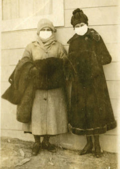 Two women wearing masks wearing fur coats
