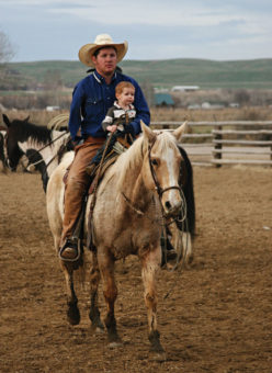 A man with his young child on a horse on a ranch.