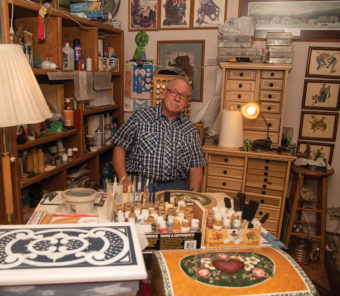 Les Tracy sitting around his woodworking and tole paintings