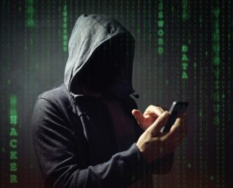 a hooded figure taps a cellphone screen