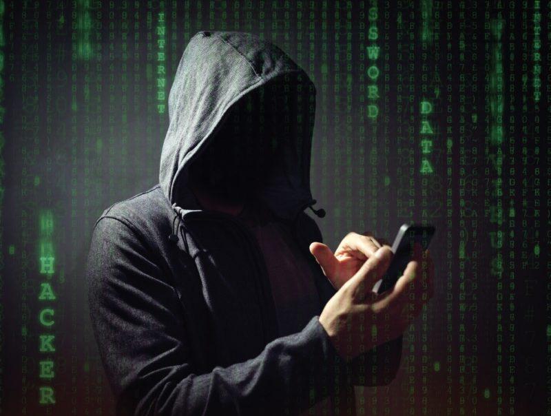a hooded figure taps a cellphone screen