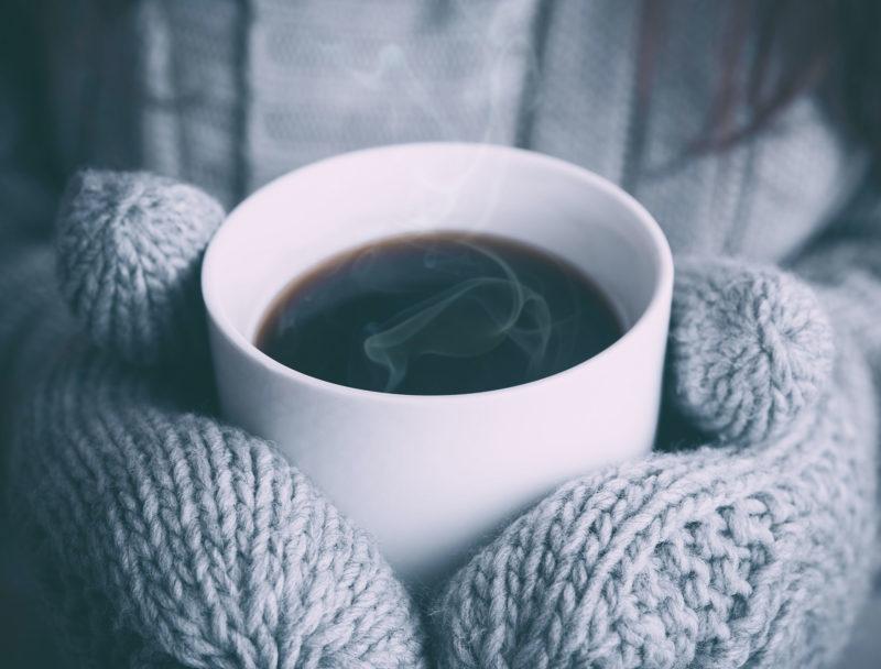 gloved hands holding mug with warm drink