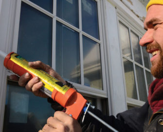 man caulking window
