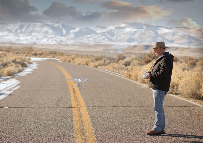man stands on desert road while piloting hovering drone