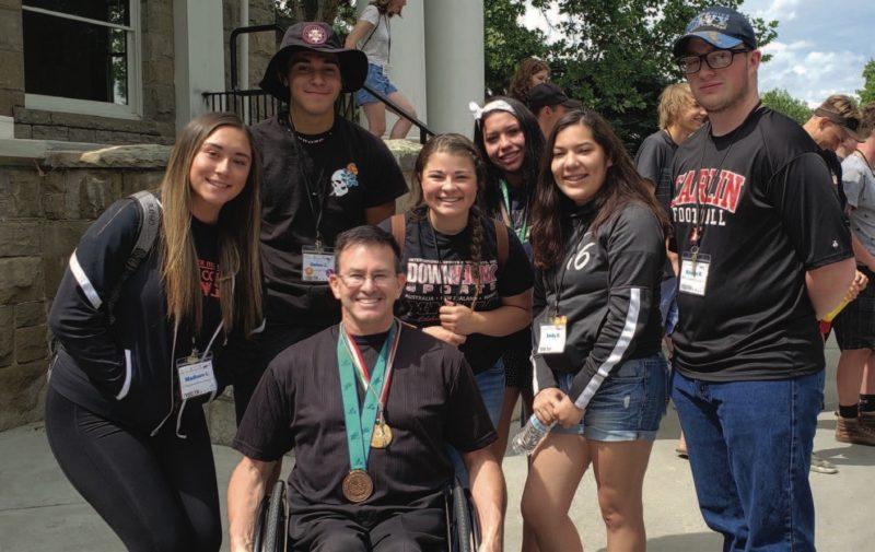 ICUA Youth Rally participants (from left) Madison Liggens, Delen Johnny, Allysa Murphy, Sandra Casas, Emily Ramirez and Raiden Ross pose with 2019 keynote speaker Mike Schlappi. Photo by Layla Walz